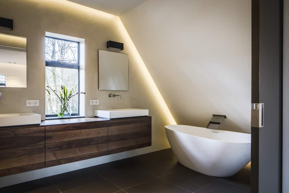 Kloostervilla ontwerp badkamer met beton cire origineel raam schuine kap indirecte verlichting badkuip wasbak