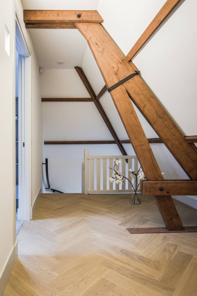 Kloostervilla interieur zolder met originele details en trap naar beneden