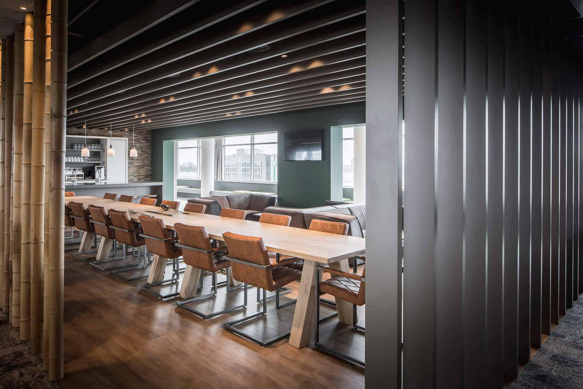 Klap scheiding tussen twee ruimten met bamboe scheidingswand links de bar en lange tafel