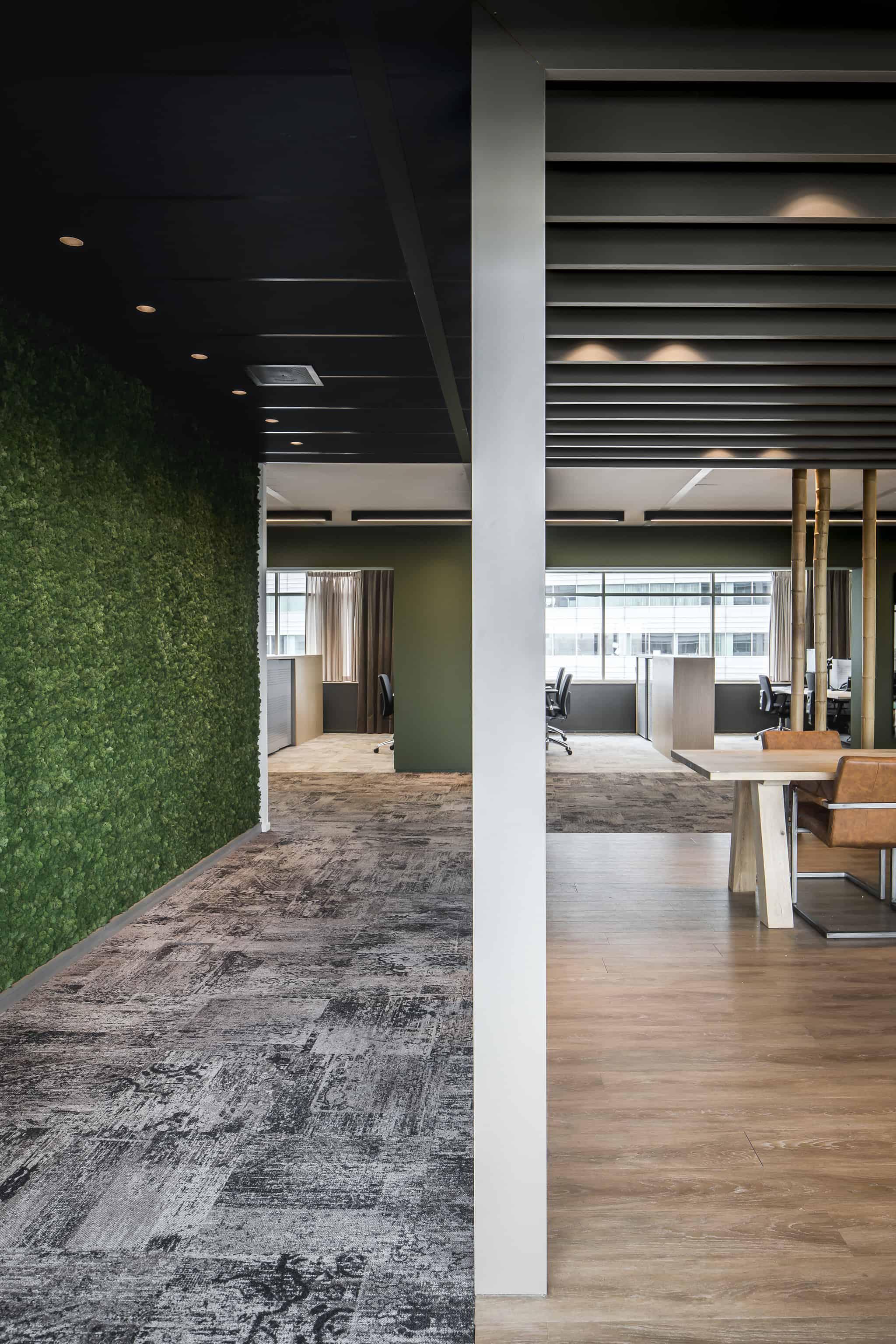 Klap ontwerp kantoor met mos op de linker wand en rechts bureau's