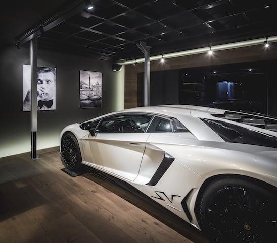 Lamborghini in het wit met zwarte velgen in zijn eigen man cave kelder te bedienen met een lift naar boven en beneden