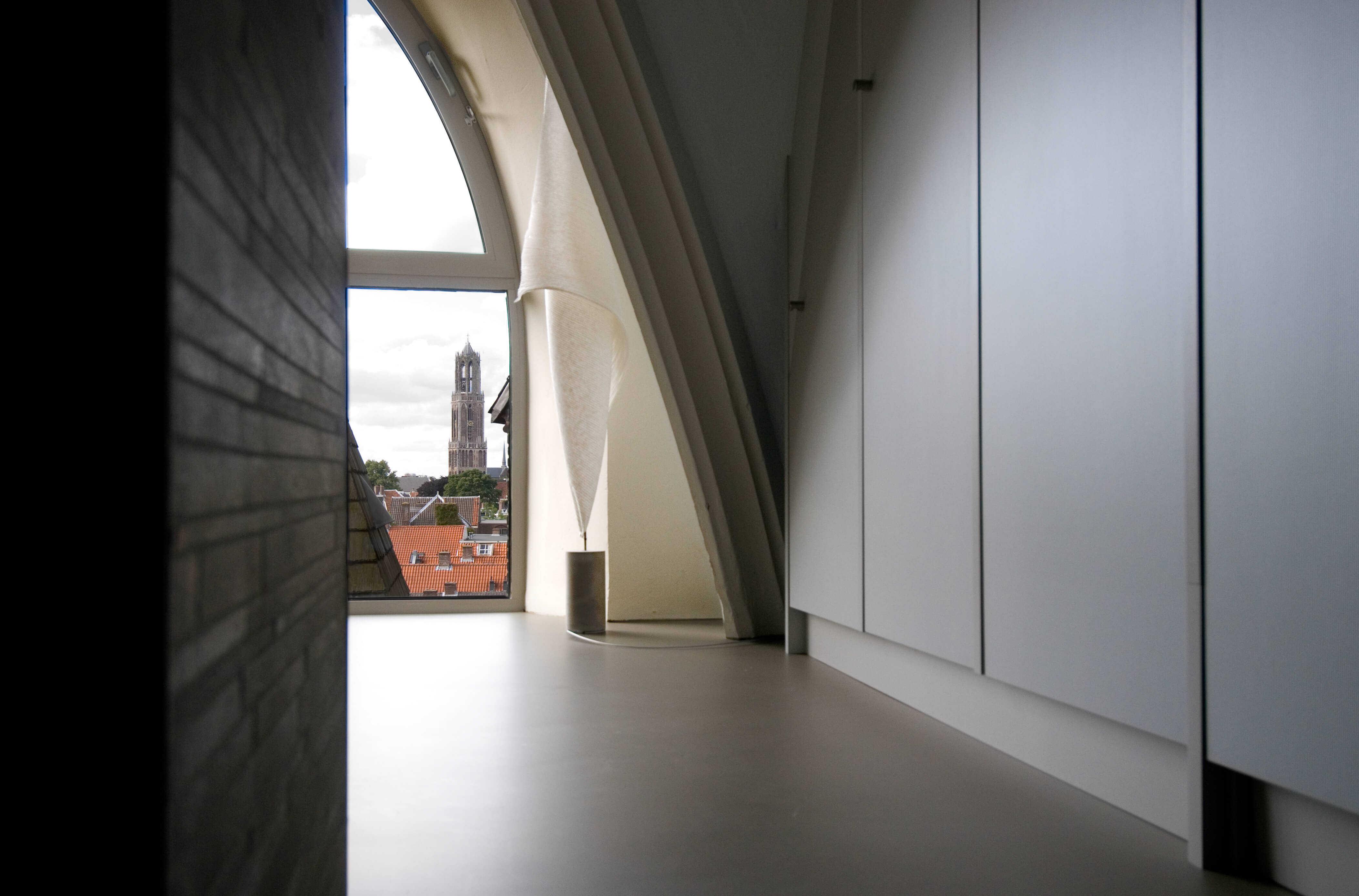 Penthouse in een kerk met uitzicht op de Domtoren in Utrecht gietvloer en kastenwand op maat gemaakt