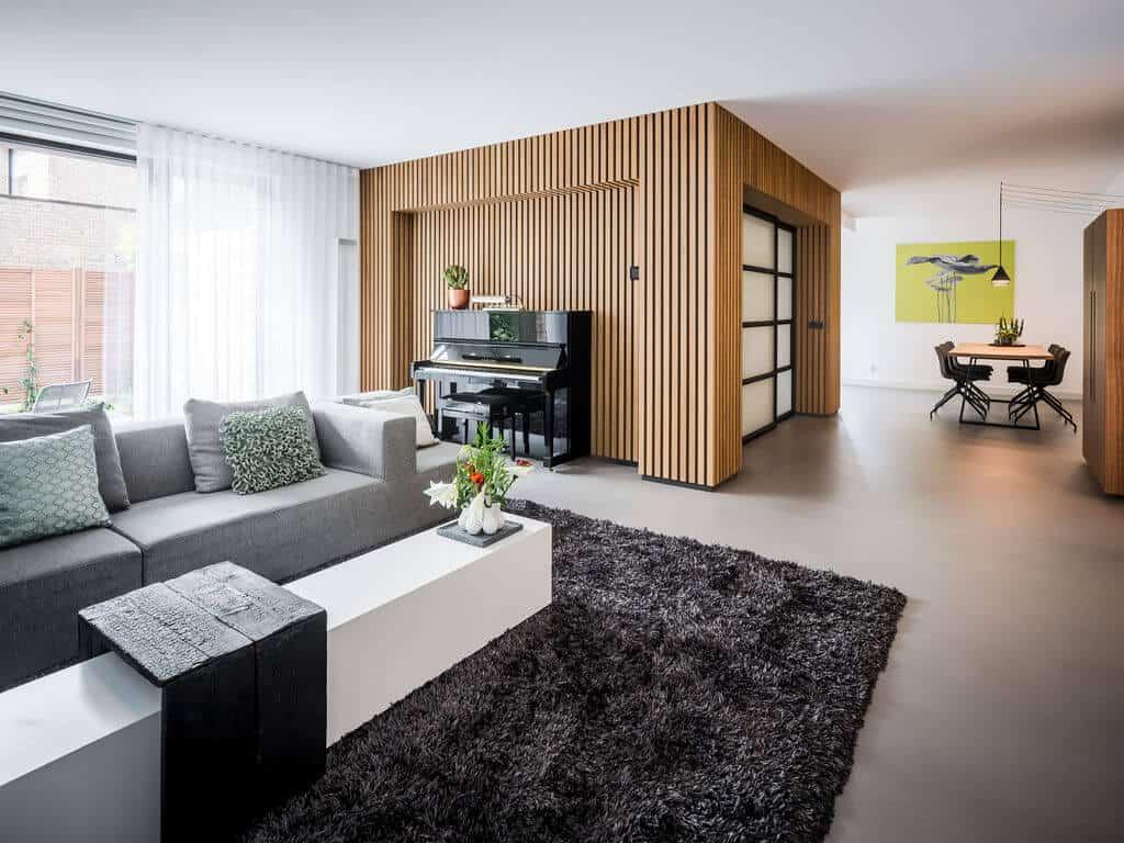 interieurarchitect Stan Wildenberg ontwerp interieur woonkamer living stalen schuifdeuren houten wanden karpet servieskast hanglampen gietvloer karpet